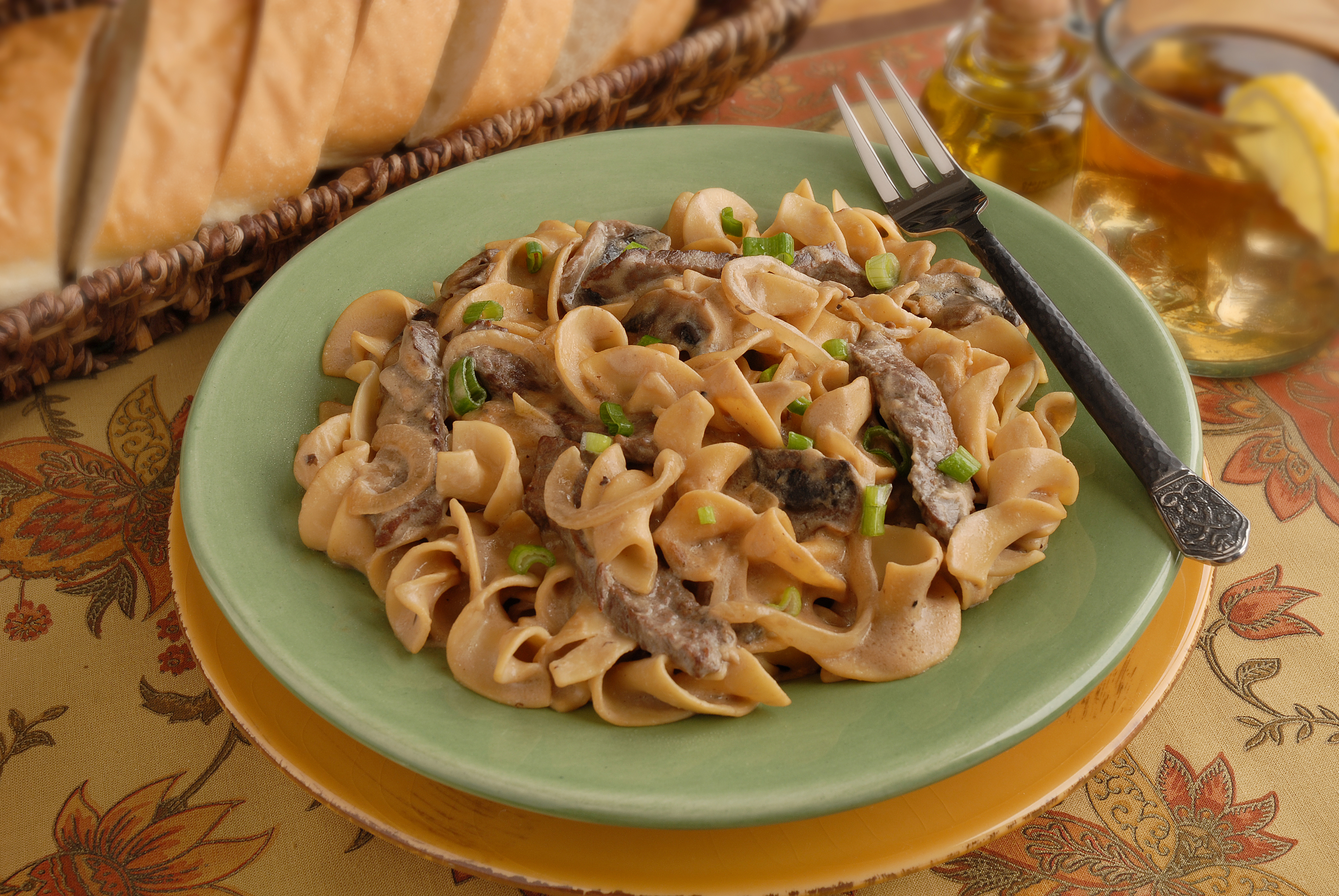 Egg noodles, beef, onions, and mushrooms in a light sauce, topped with fresh green onion